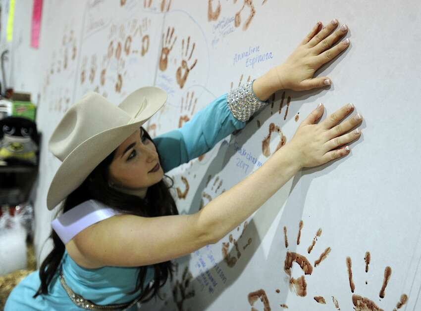 Krista Angst, 18, from Blackwell, Texas, puts a handprint on the wall of snake skinners during the 59th annual World's Largest Rattlesnake Roundup on Saturday, March 11, 2017, at the Nolan County Coliseum in Sweetwater, Texas. (Tommy Metthe/The Abilene Reporter-News via AP)