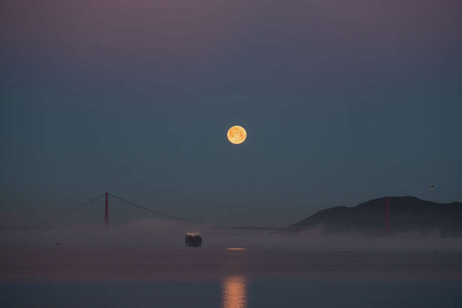 "With daylight savings time upon us and spring a little over a week away, this was the last full moonset of the winter. ""I didn't plan on shooting the moon until I saw clear skies early this morning and rushed to drive to my favorite spot along the bay,"" said photographer Voltaire Yap. Photo: Voltaire Yap"