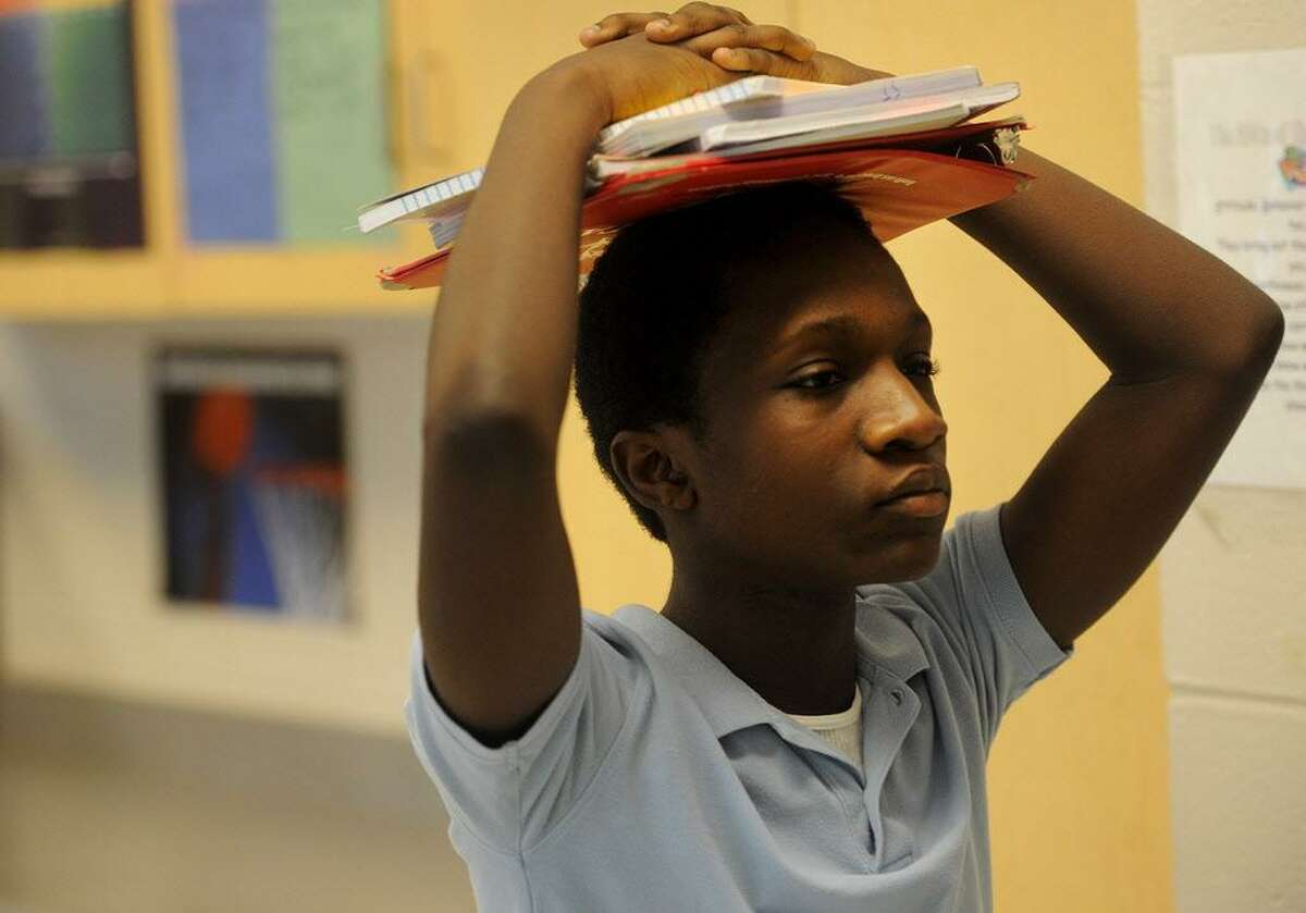 Eighth grader Lorenza Neson carries his books on his head as he leaves his Algebra class at Jettie Tisdale School in Bridgeport, Conn. on Wednesday, September 14, 2016. Eaddy's teacher Liz Capasso testified in the CCJEF trial which resulted in a recent judge's ruling demanding sweeping changes to school funding.