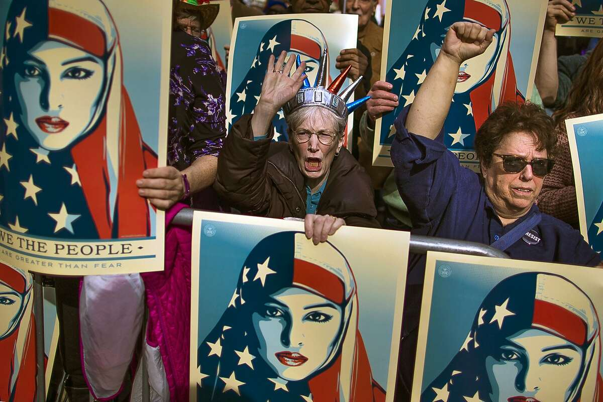 Protesters carry posters during a rally against President Trump's executive order banning travel from seven Muslim-majority nations, in New York's Times Square on Feb. 17.