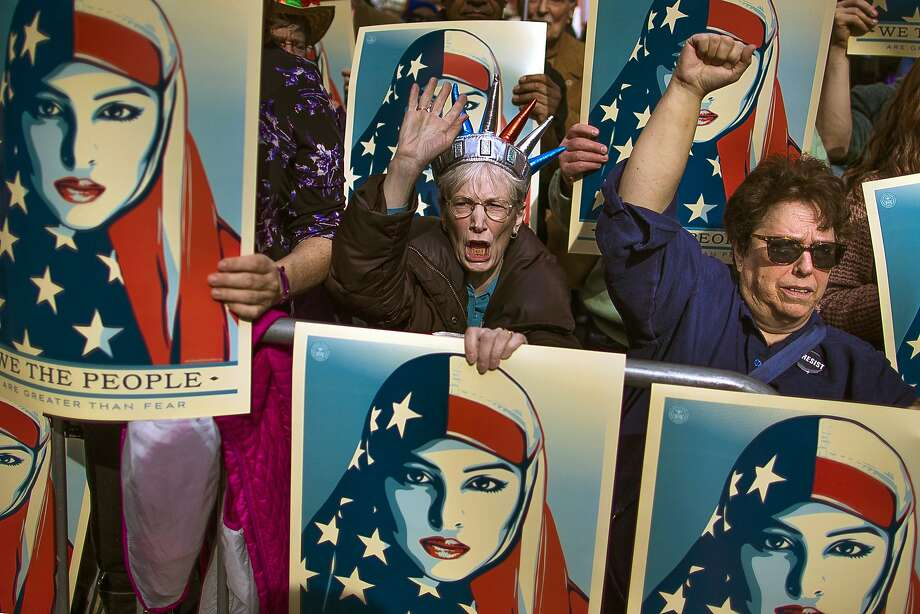 Protesters carry posters during a rally against President Trump's executive order banning travel from seven Muslim-majority nations, in New York's Times Square on Feb. 17. Photo: Andres Kudacki, Associated Press
