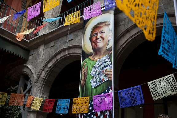 FILE - In this Nov. 10, 2016 file photo, a banner with an image of Donald Trump to promot an exhibition that features dozens of works by Mexican and international cartoonists, mocking amongst other things the U.S. president derogatory statements about Mexicans and his plans to build a wall between the two countries, in downtown Mexico City. If there are plans to take the Trump brand to Mexico, it could be tough going due to widespread popular anger toward the president for his comments disparaging Mexican immigrants who come to the United States illegally, his threats to tear up the North American Free Trade Agreement and his vows to make Mexico pay for the border wall. (AP Photo/Rebecca Blackwell, File)