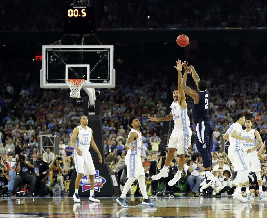 In this April 4, 2016, file photo, Villanova's Kris Jenkins makes the game-winning three-point shot during the second half of the NCAA Final Four tournament college basketball championship game against North Carolina, in Houston. The March Madness basketball tournament begins Tuesday, with many games taking place during the day when you're supposed to be working. Fortunately for you — but not your bosses — all NCAA Tournament games will be available online. North Carolina players are, from left: Brice Johnson (11), Joel Berry, Isiah Hicks (4), Justin Jackson (44) and Marcus Paige (5). Nearly a year after Jenkins' shot, the Wildcats and Tar Heels are both No. 1 seeds in the NCAA Tournament. (AP Photo/David J. Phillip, File) Photo: David J. Phillip /Associated Press / Copyright 2017 The Associated Press. All rights reserved.