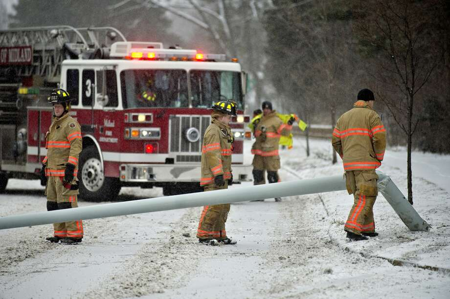 Midland fire fighters inspect a fallen light pole while working the scene of an accident on north bound Saginaw Road near Trinity Court on Monday. A vehicle traveling on Saginaw Road lost control and hit a light pole, causing it to fall into the road. A Nixle alert was sent out by Midland County Central Dispatch just after 11 a.m. Two other vehicles got into minor fender bumps avoiding the crash. No one was hurt, officials stated. Photo: NICK KING | Nking@mdn.net