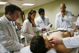 MIAMI - APRIL 02:  (L-R) James Sikora, Kay Schmid, Shravan Kandula and Allen Sanchez all third year medical students at The Gordon Center for Research In Medical Education, University of Miami, attend a class where they work with Harvey, the cardiopulmonary patient simulator on April 2, 2009 in Miami, Florida. Despite the weak economy there is a need for health care workers, which is reflected in the rise of applications for the University of Miami medical school. Recently a report by Association of American Medical Colleges said the shortage is expected to exceed 124,000 physicians by 2025, and it will be most acute in primary care. (Photo by Joe Raedle/Getty Images)