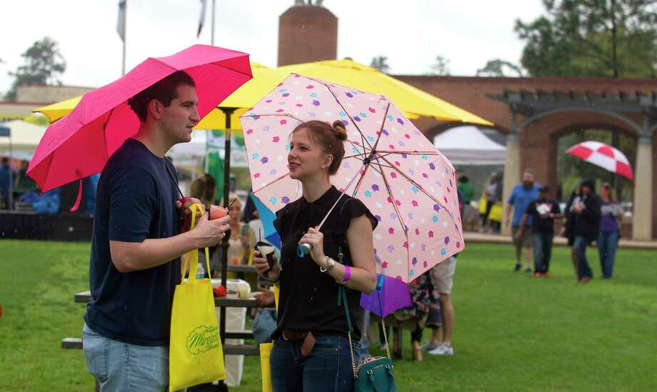 Colin and Kirstina Jefferies enjoy margaritas in the rain under the cover of their umbrellas during The Woodlands Margarita Festival at Town Green Park on Saturday, March 11, 2017, in The Woodlands. Photo: Jason Fochtman / Conroe Courier / HCN