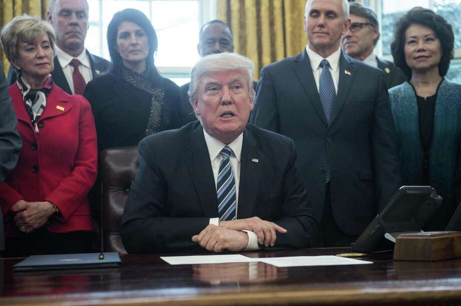 President Donald Trump, surrounded by members of his cabinet Monday, speaks before signing an executive order entitled Comprehensive Plan for Reorganizing the Executive Branch in the Oval Office at the White House. (Nicholas Kamm / AFP/Getty Images) Photo: NICHOLAS KAMM, Staff / AFP or licensors