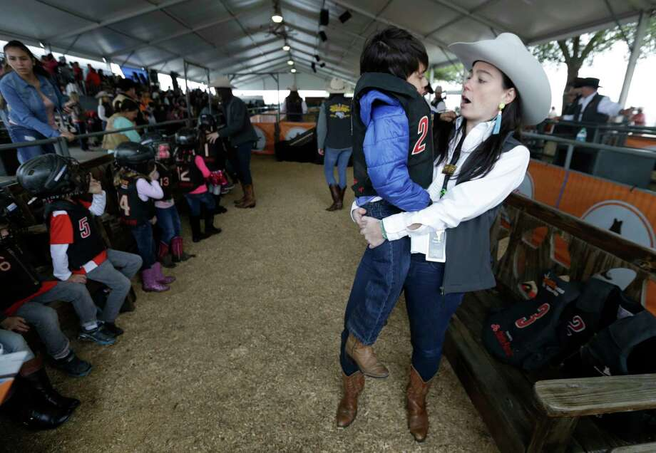 Bobbi Ingram, left, with the Mutton Bustin committee, talks with Benjamin Mancillas, 6, after his ride during the Houston Livestock Shown and Rodeo at NRG Center, Monday, March 13, 2017, in Houston. He lost a tooth that was already loose. Photo: Melissa Phillip, Houston Chronicle / © 2017 Houston Chronicle