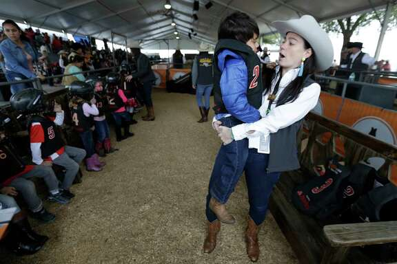 Bobbi Ingram, left, with the Mutton Bustin committee, talks with Benjamin Mancillas, 6, after his ride during the Houston Livestock Shown and Rodeo at NRG Center, Monday, March 13, 2017, in Houston. He lost a tooth that was already loose.