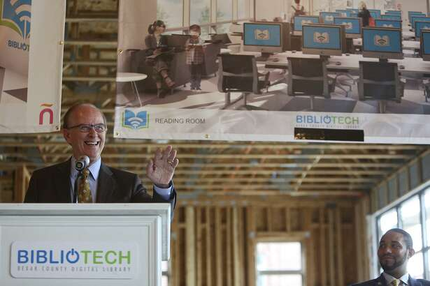County Judge Nelson Wolff speaks as County Commisioner Tommy Calvert, right, watches during an event for the new BiblioTech digital library facility under construction at the East Meadows housing development on Monday, March 13, 2017.