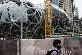 A man walks past the Amazon biospheres  construction site in downtown Seattle on Oct. 21, 2017.