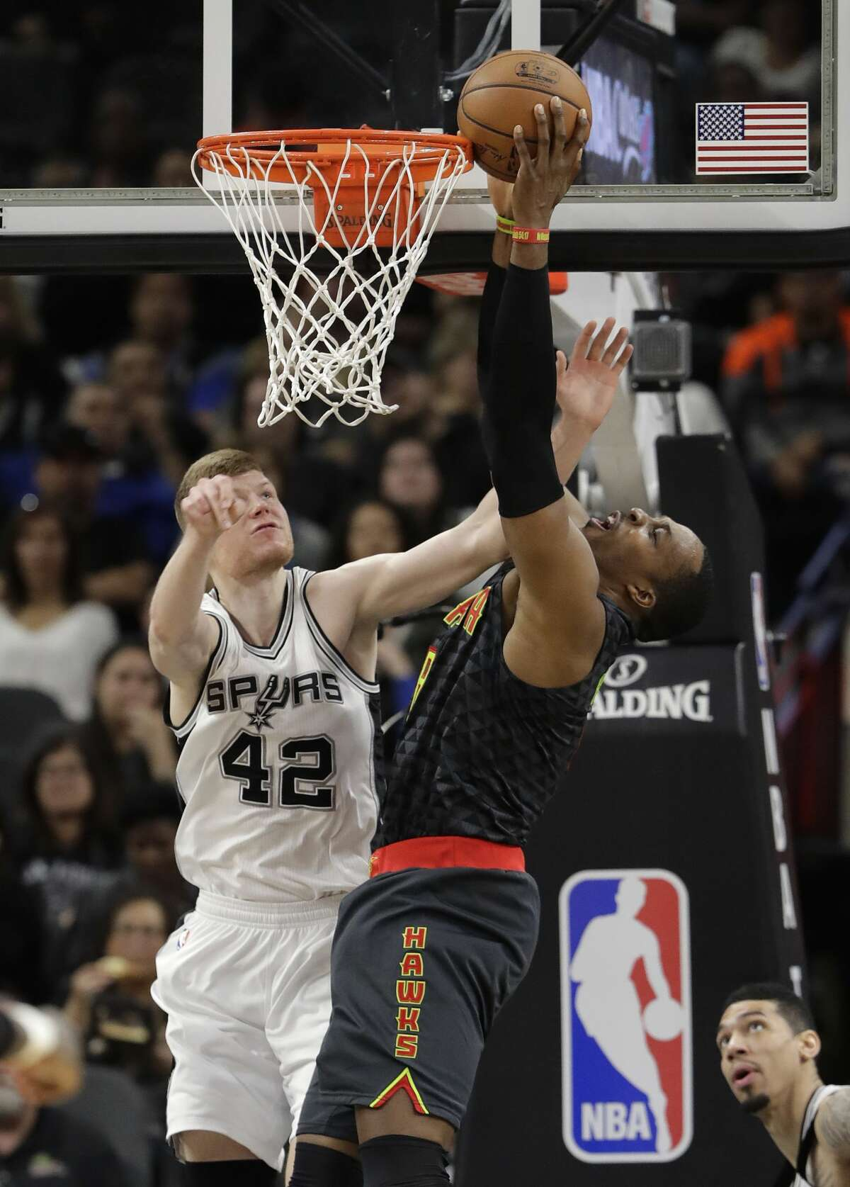 Atlanta Hawks center Dwight Howard, right, is fouled by San Antonio Spurs forward Davis Bertans (42) as he tries to score during the first half of an NBA basketball game, Monday, March 13, 2017, in San Antonio. (AP Photo/Eric Gay)