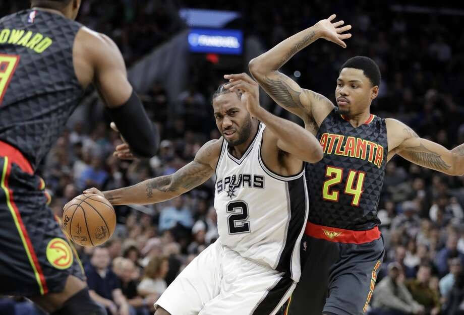 San Antonio Spurs forward Kawhi Leonard (2) drives around Atlanta Hawks forward Kent Bazemore (24) during the first half of an NBA basketball game, Monday, March 13, 2017, in San Antonio. (AP Photo/Eric Gay) Photo: Eric Gay/Associated Press