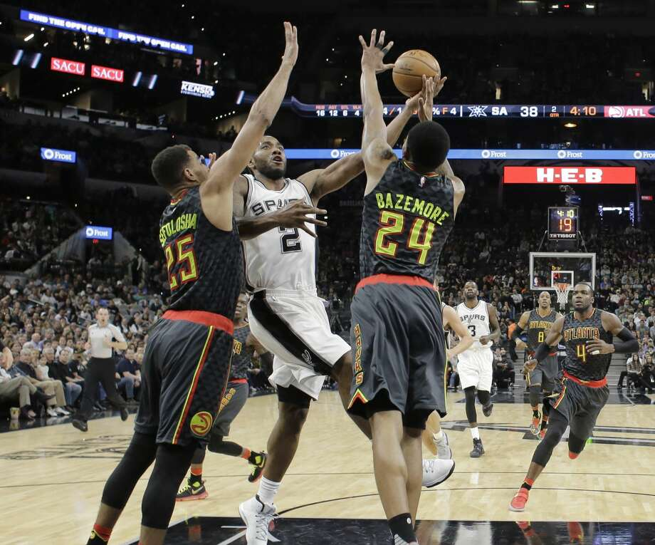 San Antonio Spurs forward Kawhi Leonard (2) drives to the basket against Atlanta Hawks defenders Thabo Sefolosha (25) and Kent Bazemore (24) during the first half of an NBA basketball game, Monday, March 13, 2017, in San Antonio. (AP Photo/Eric Gay) Photo: Eric Gay/Associated Press