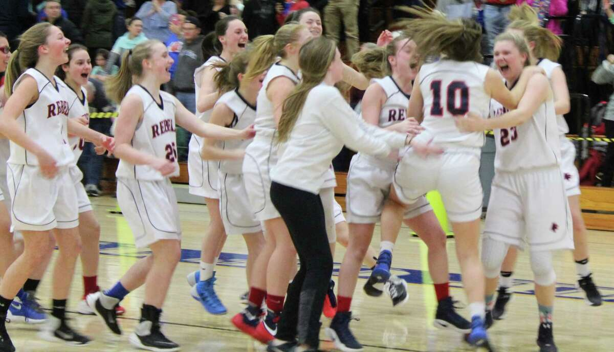 Sydney Gouveia (10) is mobbed by her celebrating teammates after she hit the winning shot at the buzzer in New Fairfield's victory over Waterford in the Class M girls basketball state semifinals at Newington High School March 13, 2017.