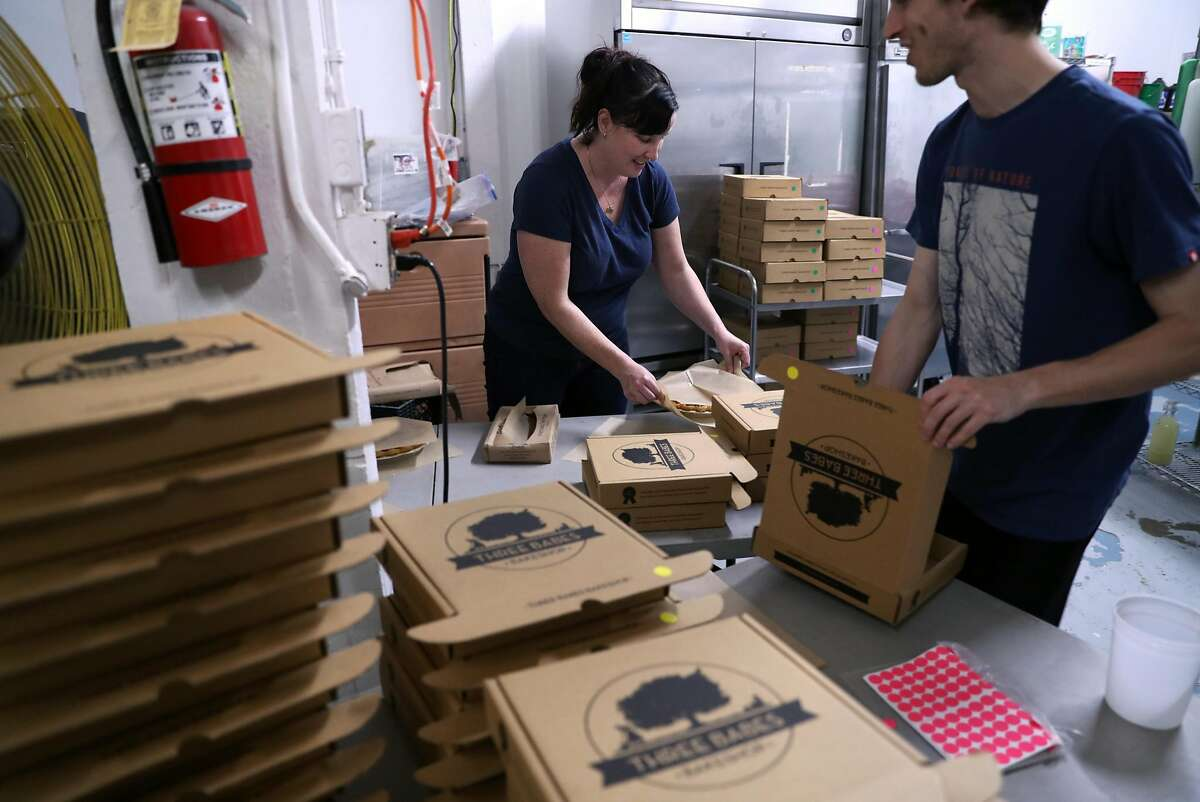 Nick Goelz (right) and Colleen McGarry build pie boxes as Three Babes Bakeshop prepares for Pi Day in San Francisco, Calif., on Monday, March 13, 2017.