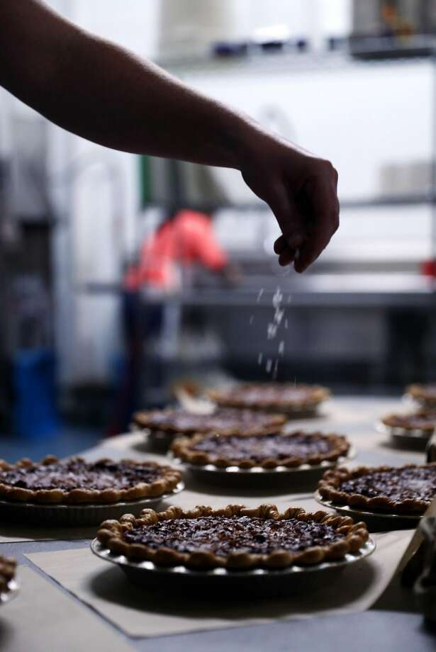 Colleen McGarry sprinkles salt on honey walnut pies at Three Babes Bakeshop in San Francisco during busy preparations on the eve of Tuesday's celebration of Pi Day. Photo: Scott Strazzante, The Chronicle