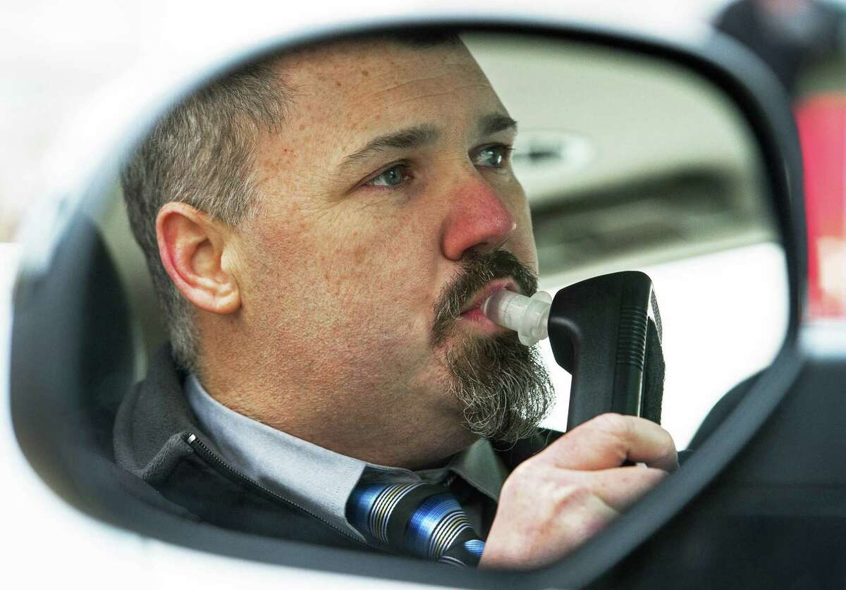 Bill Chastain, State Director with LifeSafer, is seen in the mirror of his car as he demonstrates a breath alcohol ignition interlock on Dec. 17, 2013 in Washington, DC.