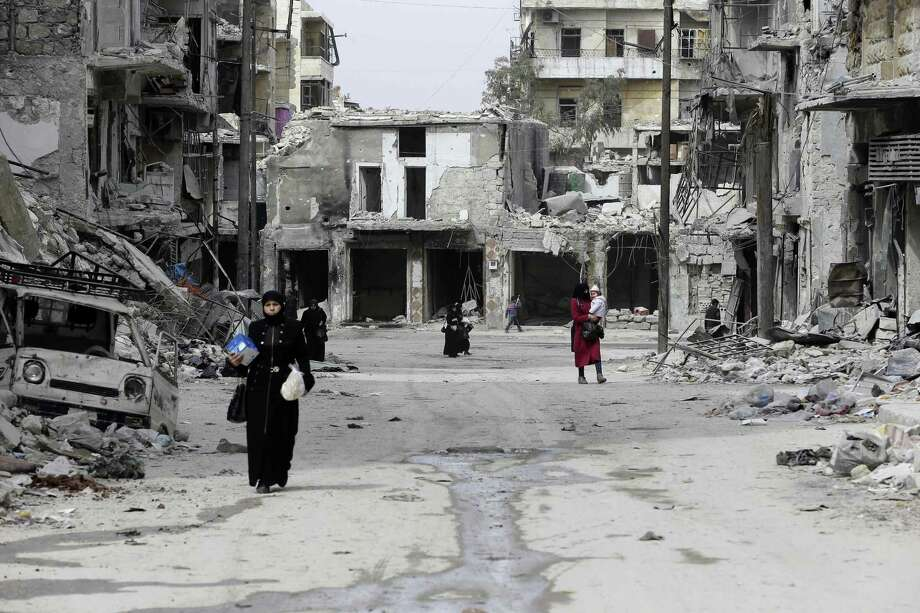 A picture taken on March 9, 2017 in the northern Syrian city of Aleppo, which was recaptured by government forces in December 2016, shows people walking past heavily damaged buildings in the formerly rebel-held al-Shaar neighbourhood.  / AFP PHOTO / JOSEPH EIDJOSEPH EID/AFP/Getty Images Photo: JOSEPH EID, Staff / AFP/Getty Images / AFP or licensors