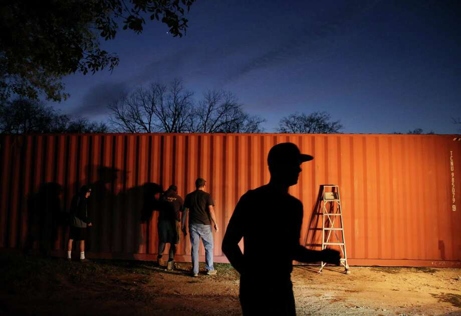 """A group of teenagers from The Church of Jesus Christ of Latter Day Saints and Boy Scout Troop 1042 paint a ship container that would become a house for a homeless veteran when it is completed Wednesday, March 1, 2017, in Montgomery. This was the first """"tiny house"""" that the Montgomery-based nonprofit Green Zone Housing started and hoped to continue. ( Yi-Chin Lee / Houston Chronicle ) Photo: Yi-Chin Lee, Staff / Houston Chronicle / © 2017  Houston Chronicle"""
