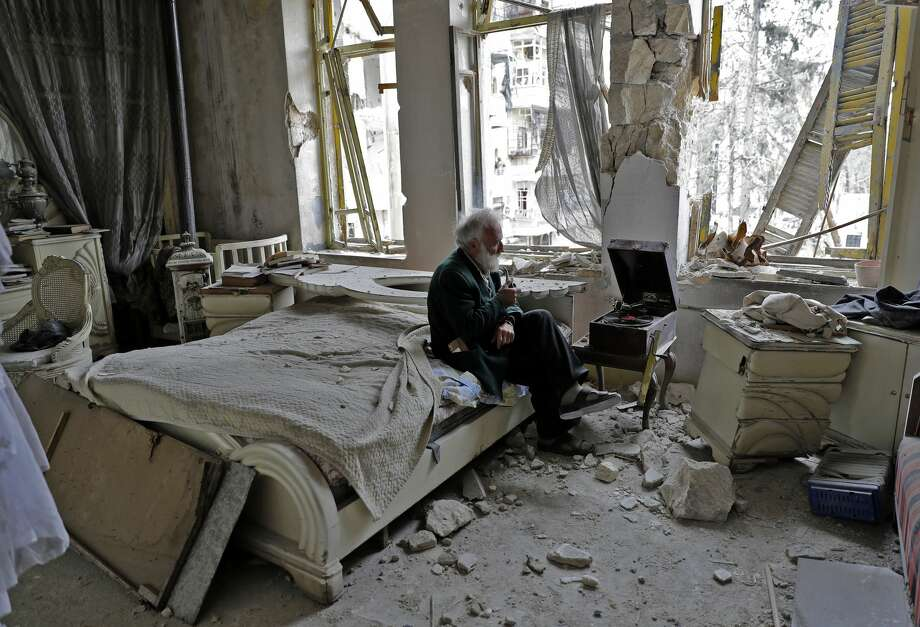 Mohammad Mohiedine Anis, 70, smokes his pipe as he sits in his destroyed bedroom listening to music on his vinyl player, gramophone, in Aleppo's formerly rebel-held al-Shaar neighbourhood. Photo: JOSEPH EID/AFP/Getty Images
