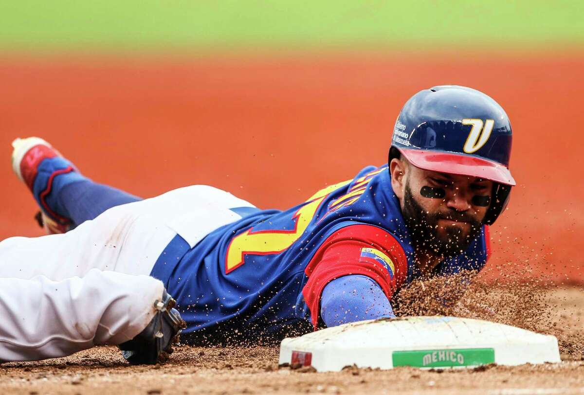 Venezuela's Jose Altuve dives back to first base in the sixth inning of a World Baseball Classic game against Italy, in Guadalajara, Mexico, Saturday, March 11, 2017. (AP Photo/Luis Gutierrez)