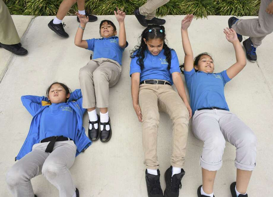 """Melody Carranza, left, Kimberly Gonzalez, Kalicia Martinez and Stephanie Diaz do sit-ups during third and fourth grade physical education class at IDEA Monterrey Park on Friday, March 3, 2017. The """"Healthy Kids Here"""" initiative aims to encourage students to achieve and maintain good health. Photo: Billy Calzada, Staff / San Antonio Express-News / San Antonio Express-News"""