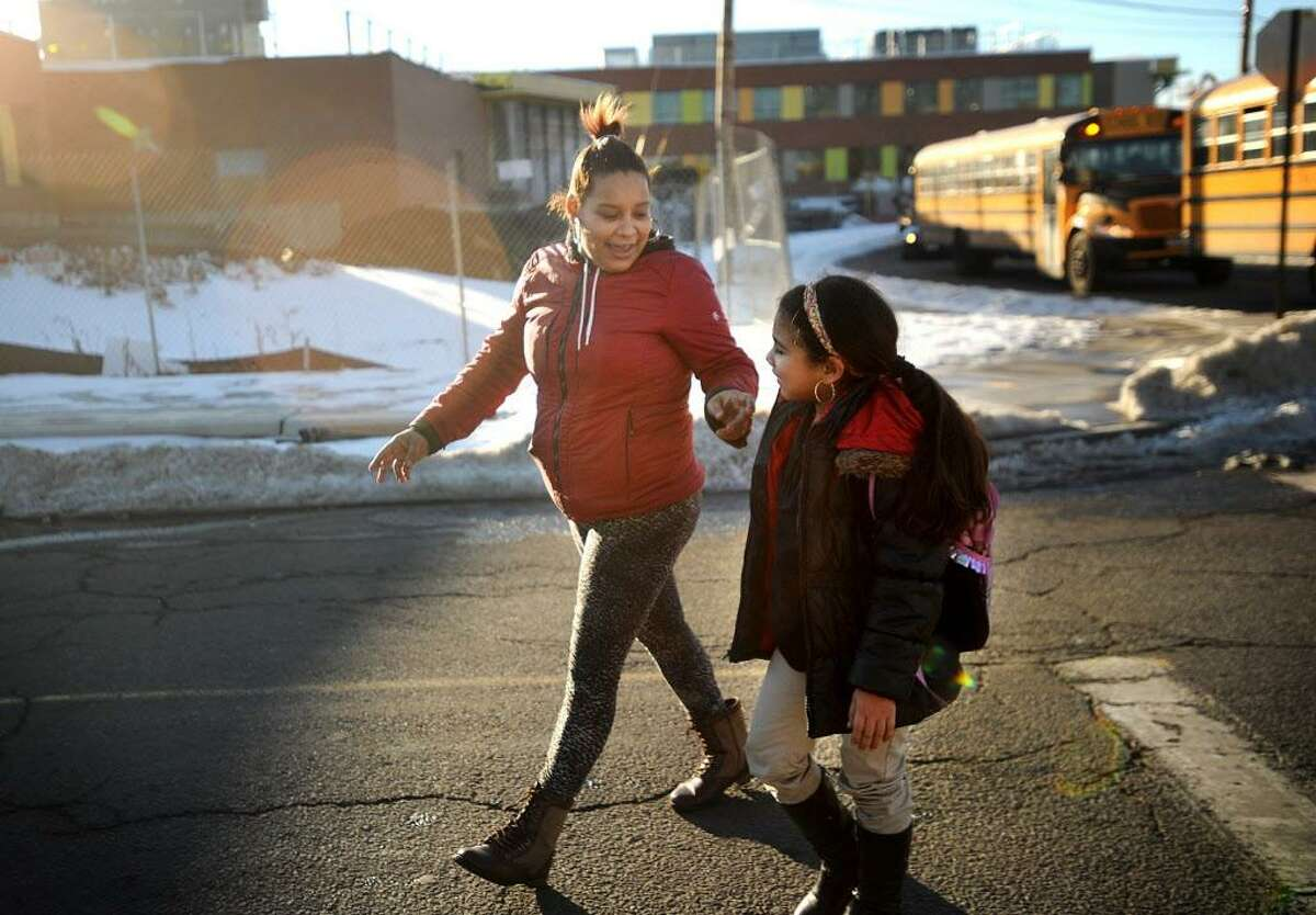 Jessenia Rios, of Bridgeport, picks up her daughter Samirah Capeles, 9, as she gets off the bus from Columbus Magnet School outside the new Claytor School, still under construction on Wordin Avenue in Bridgeport, Conn. on Wednesday, January 27, 2016.