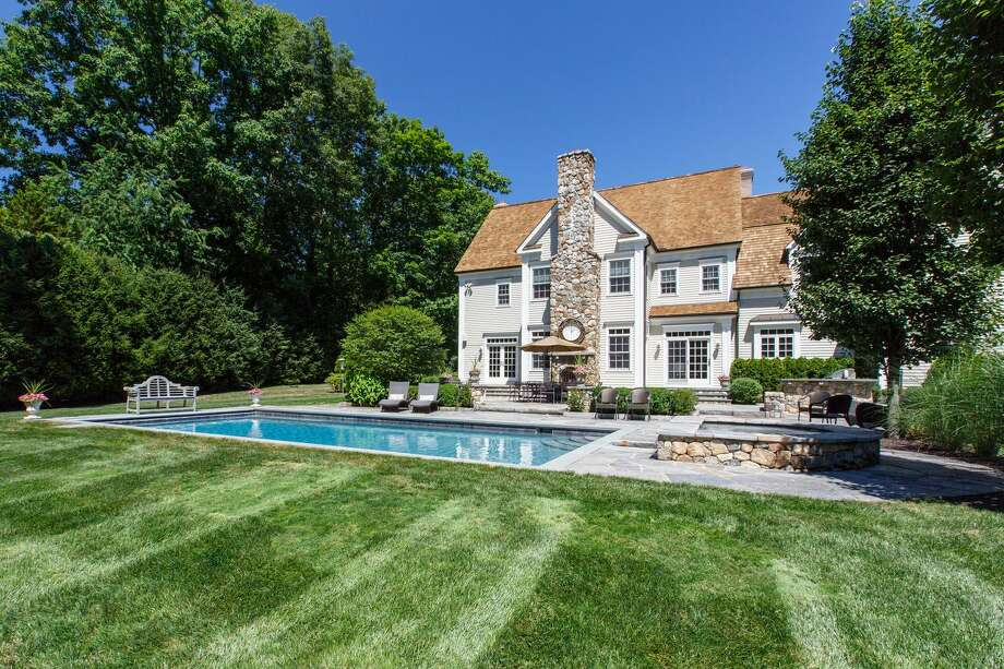 The backyard of this 13-room colonial house at 62 Norholt Drive has an outdoor kitchen, outdoor fireplace, large bluestone patio and a heated in-ground pool and spa. Photo: Contributed Photo / Michael W Smith