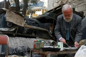 ALEPPO, SYRIA - APRIL 10: Antiquarian Syrian doctor Mohamed Mohideen Enis Abu Omar is eating his meal among his antique pieces in Aleppo, Syria on April 10, 2015. Despite the all negative effects of the war, Syrian doctor Mohamed Mohideen Enis Abu Omar, doesn't abandon any of the antique pieces of his collection including 24 antique cars and many priceless antiques. (Photo by Ahmed Muhammed Ali/Anadolu Agency/Getty Images)