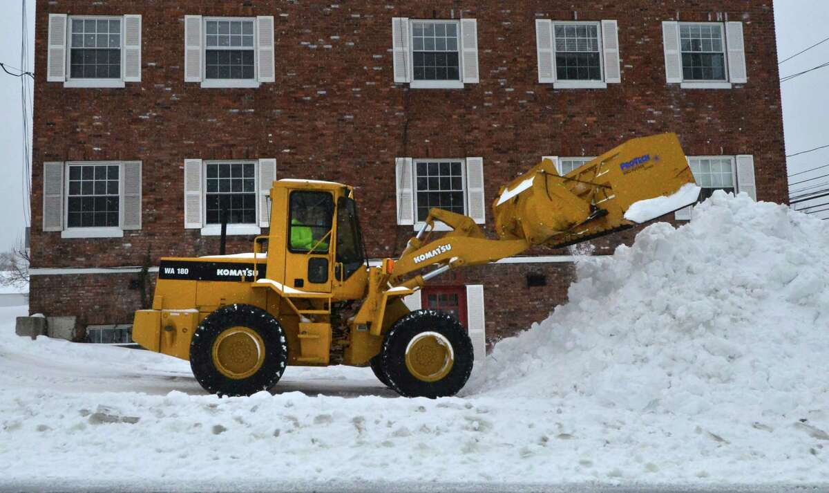 A loader is used to clear and pile snow from the parking lot of a medical building during the Nor'easter that brought heavy snow, wind and mixed precipitation through Norwalk Conn. on Tuesday March 14, 2017.