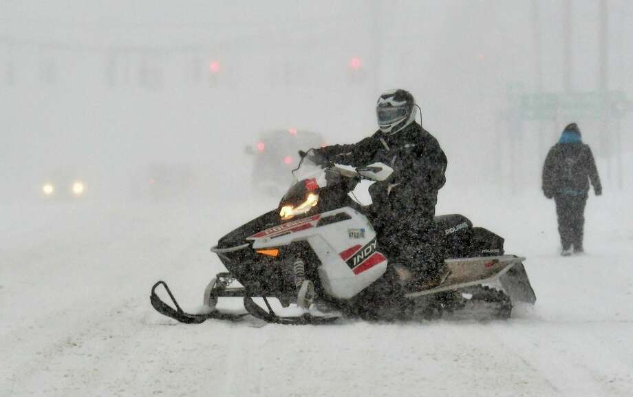 A snowmobile makes it way down Central Avenue on Tuesday, March 14, 2017. (John Carl D'Annibale/Times Union) Photo: John Carl D'Annibale/Times Union