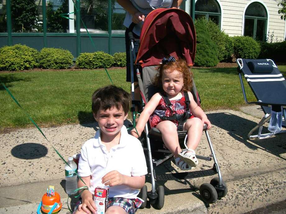 Owen White, 4, and his sister Avery, one-and-a-half, sit curbside on Post Road in Darien on Monday, awaiting their first-ever Darien Memorial Day Parade. Photo: Maggie Gordon / Darien News