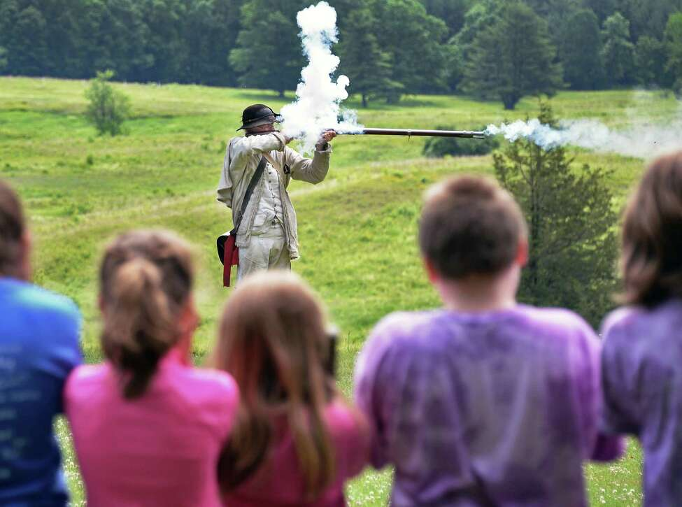 Park Ranger Joe Craig fires a flintlock as he instructs Broadalbin-Perth fourth graders in musket drills during their field trip to Saratoga National Historical Park on Thursday, June 16, 2016, in Stillwater, N.Y. (John Carl D'Annibale / Times Union)