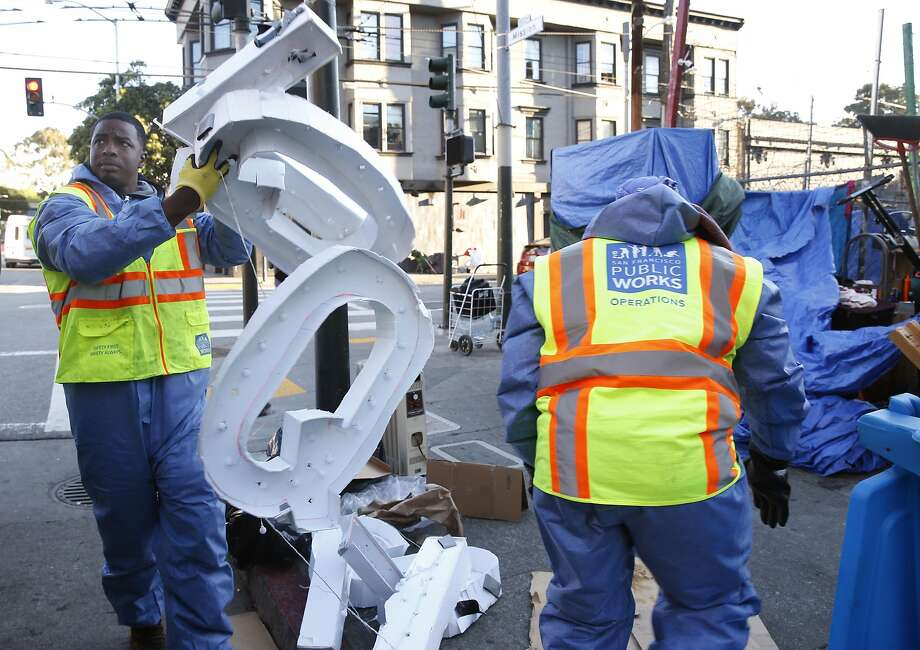 A Public Works Hot Spots crew clears out a homeless encampment at 14th and Mission streets before sanitizing the sidewalk. Photo: Paul Chinn, The Chronicle