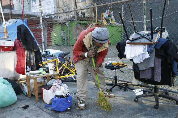 Markael Rayvon gathers his belongings after the homeless encampment he was living in was taken down at 14th and Mission streets before a Public Works Hot Spots crew can clean up and disinfect the sidewalk in San Francisco, Calif. on Tuesday, March 14, 2017.