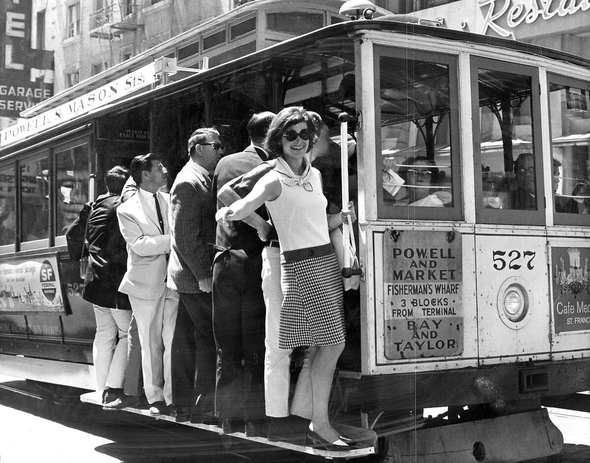 Sandy Krentzman of Los Angeles rides a San Francisco cable car -- shortly after a rule banning women from standing on the steps was lifted. April 27, 1965.