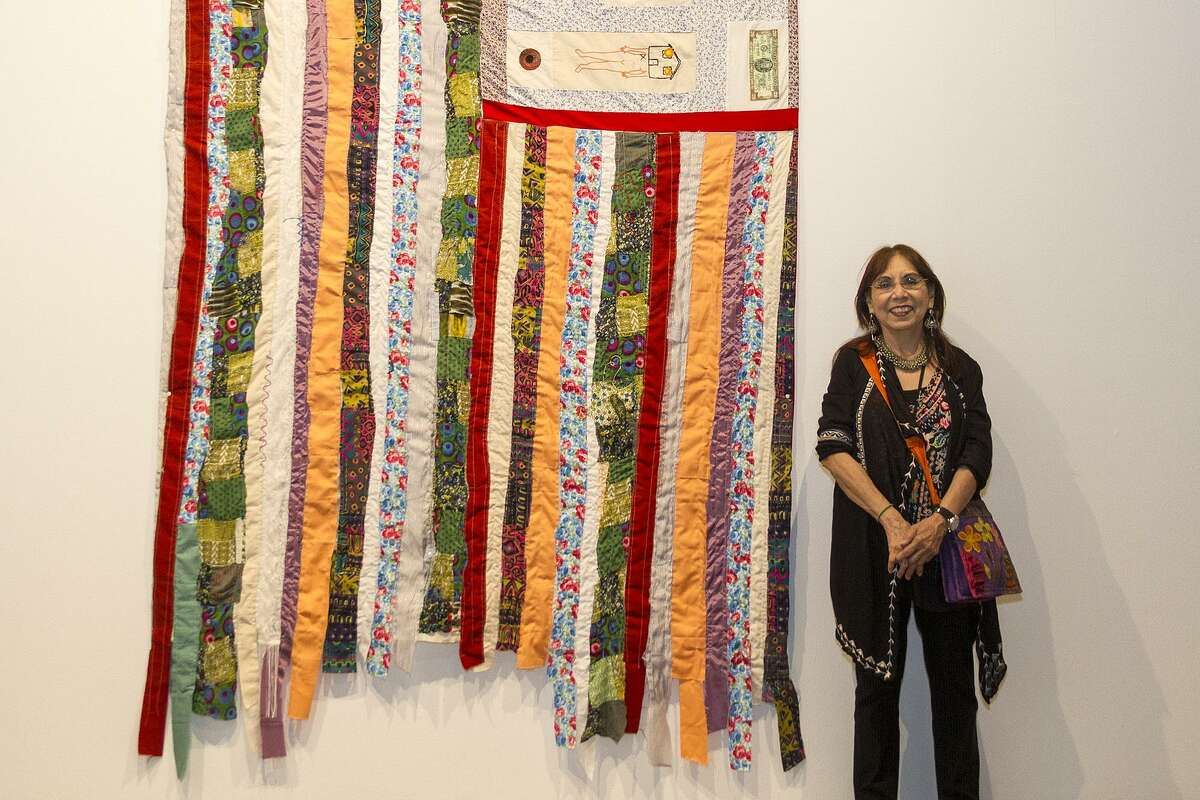 """Kathy Vargas, who curated """"A Woman's Place ...,"""" stands with a piece by Jenelle Esparza that is part of the Centro de Artes exhibit."""