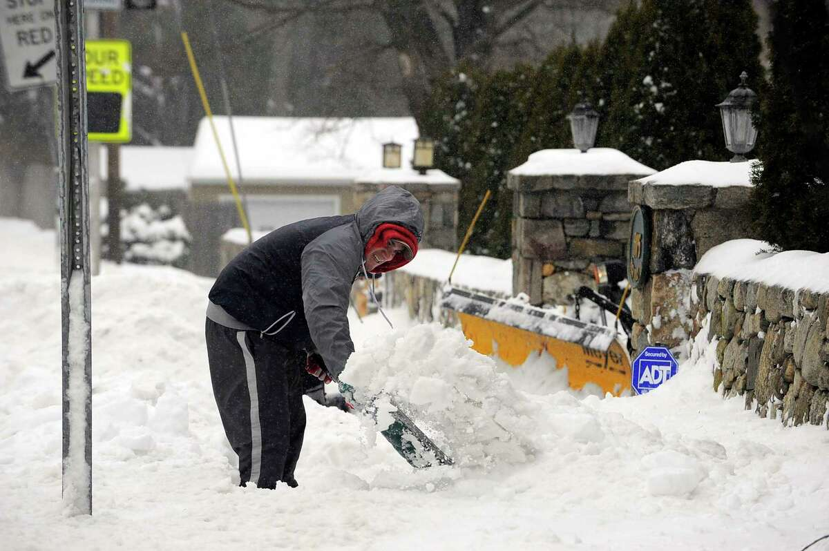 Elder Valdez clears snow for an elderly resident during a winter storm in Stamford, Conn. on March 14, 2017.