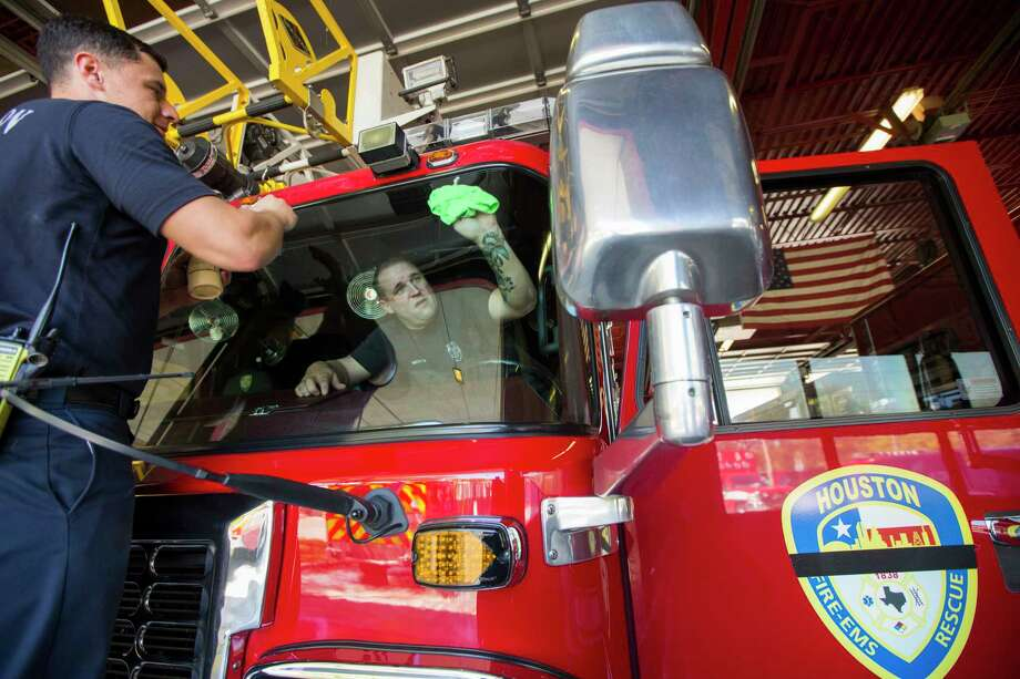 """Houston firefighters Chris Hernandez and Paul Williams clean the windows on HFD Ladder 68 as they help prepare it for the public memorial service for Houston Fire Capt. William """"Iron Bill"""" Dowling on Tuesday, March 14, 2017, in Houston. Photo: Brett Coomer, Houston Chronicle / © 2017 Houston Chronicle"""