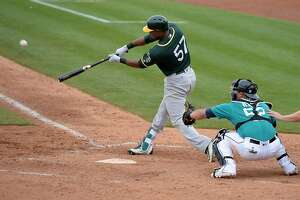 PEORIA, AZ - MARCH 05:  Alejandro De Aza #57 of the Oakland Athletics hits an RBI double in the fifth inning of the spring training game against the Seattle Mariners at Peoria Stadium on March 5, 2017 in Peoria, Arizona.  (Photo by Jennifer Stewart/Getty Images)