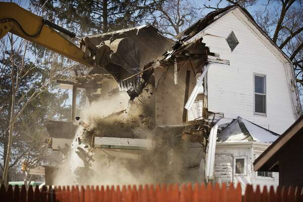A house at 410 Jerome Street is demolished on Tuesday in Midland. The Michigan Baseball Foundation bought the house  —  along with its neighbors at 402, 406 and 416  —  in the summer of 2016.