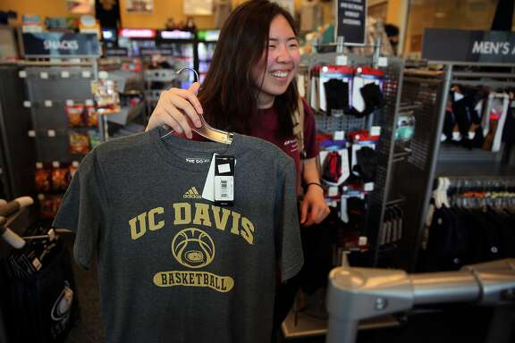 Erika Huang a clerk at the UC Davis Pro shop displays a tee shirt found in the back room of the business in Davis, Ca., on Tues. March 14, 2017, as the UC Davis Aggies have won an invitation in the NCAA basketball tournament in a first four ultra-preliminary game against North Carolina Central.
