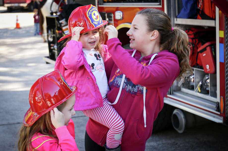 Gracie Hinson, 11, right, helps Hadley Ratto, 3, don a plastic firefighter's hat during the Safety Day presented by The Woodlands Township Neighborhood Watch on Tuesday, March 14, 2017, in front of The Woodlands Children's Museum. Photo: Michael Minasi, Staff Photographer / © 2017 Houston Chronicle