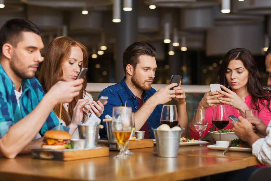 Friends with smartphones dining at restaurant. (Dreamstime/TNS) Photo: Dreamstime/TNS