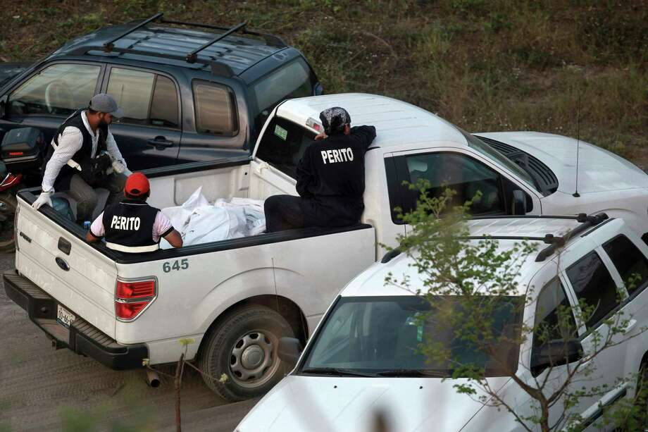 In this April 11, 2015 photo, special investigators guard bodies found in mass graves in a wooded area known as Colinas de Santa Fe on the outskirts of Veracruz, Mexico. Veracruz state's top prosecutor, Jorge Winckler, said the clandestine pits appeared to contain remains of cartel victims killed years ago. (AP Photo/Felix Marquez) Photo: Felix Marquez, STR / Copyright 2017 The Associated Press. All rights reserved.