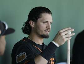 San Francisco Giants' Jarrett Parker tapes his bat before a spring training baseball game against the Arizona Diamondbacks, Sunday, March 12, 2017, in Scottsdale, Ariz. (AP Photo/Darron Cummings)