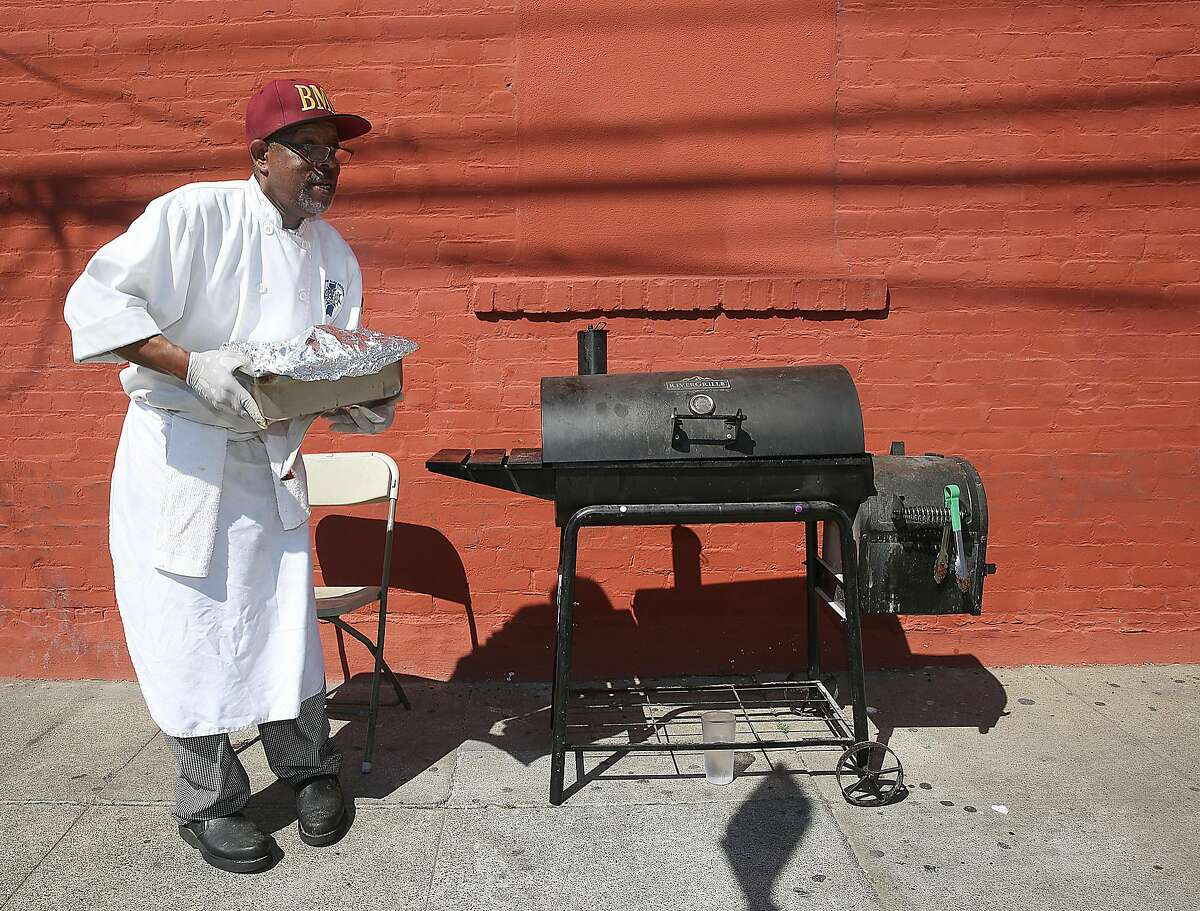 Head cook Rico Calhoun removes brisket from the smoker outside of Big Momma's Kitchen on Tuesday, March 14, 2017, in Oakland, Calif.