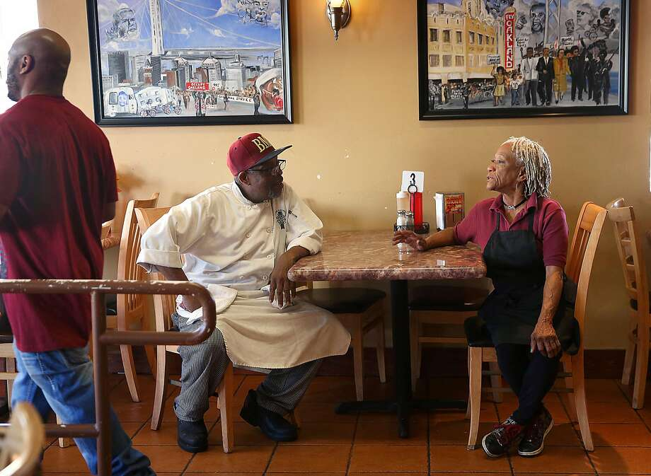 Head cook Rico Calhoun (left) and Isabella Coffey chat at Big Momma's Kitchen in Oakland. At left is Ms. Coffey's son Tyreke Coffey. Photo: Liz Hafalia, The Chronicle