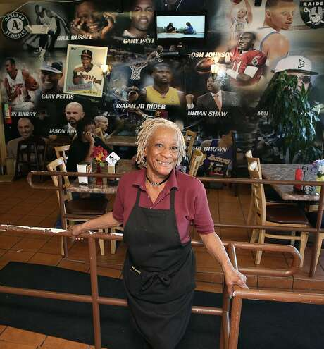 Ms. Coffey, a.k.a. Isabella Coffey, at her Big Momma's Kitchen in Oakland with its mural of Oakland sports figures behind her. Photo: Liz Hafalia, The Chronicle